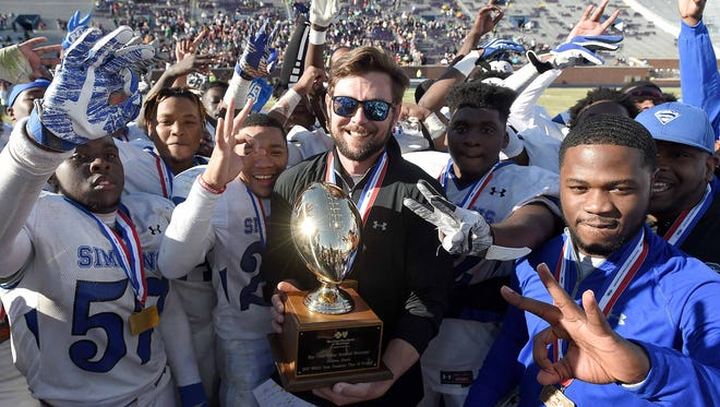 Simmons head coach Wade Tackett and the Blue Devils celebrate with the Class 1A trophy after beating Nanih Waiya 22-20.