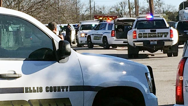 Law enforcement personnel from the Ellis County Sheriff's Office park outside a high school in Italy, Texas, following an active shooter incident at the school Monday morning, Jan. 22, 2018. Sheriff's officials said a boy who is a student at the school was taken into custody. (Jennifer Lindgren/KTVT Dallas Fort Worth via AP)