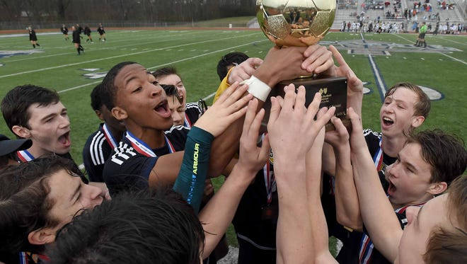 The St. Joseph Bruins celebrate with the 1A-2A-3A trophy after beating Sacred Heart 5-2 at the MHSAA Soccer State Championships, Saturday, February 18, 2018, at Ridgeland High School in Ridgeland, Miss.
