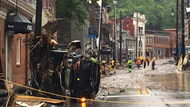 Rescue personnel walk along Ellicott City's Main Street on Sunday, May 27, 2018 in Maryland. (Libby Solomon/Baltimore Sun/TNS)