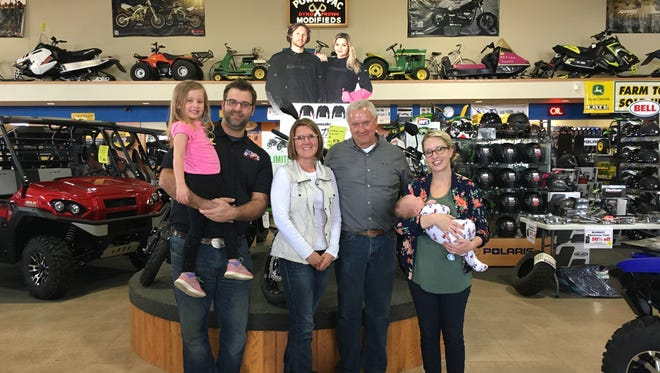 From left to right: Josh Witt, (holding Piper Witt – Josh and Mandy's daughter) Cheri Trulen, Mike Trulen, Mandy Witt (holding Graysen Witt – Josh and Mandy's son) pose for a photo after signing a buy/sell agreement regarding ownership of Power Pac Inc.