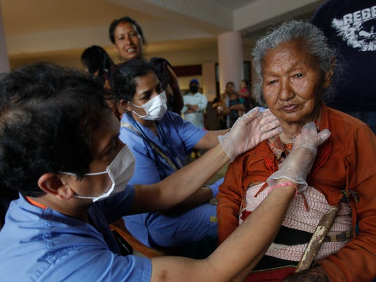 Dr. Ashish Parikh examines a goiter on the neck of an 85-year-old woman. Medical staff from the Delaware Medical Relief Team saw more than 300 patients during a clinic at Khwopa Higher Secondary School in Bhaktapur, Nepal, on Saturday.