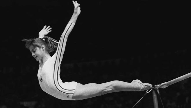 "Nadia Comaneci, of Romania, dismounts from the uneven parallel bars during a perfect ""10"" performance at the Summer Olympics in Montreal."
