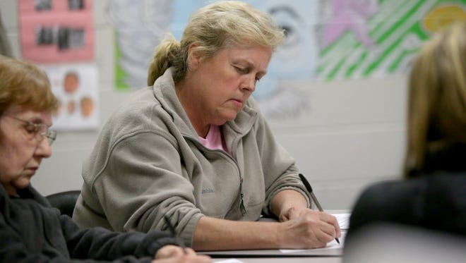 Terrill Byard, a resident of Old Plantation Subdivision, fills out a questionnaire during a public meeting held by the Germantown Municipal School District as they consider locations for a new elementary school.