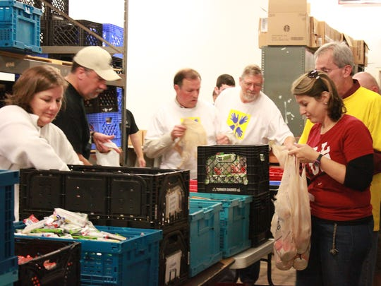 Jackson Sun employees and family members pack bags of food Saturday at the Regional Inter-Faith Association. Saturday was Make A Difference Day, the nation's largest day of community service