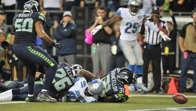 Kam Chancellor knocks the ball out of Calvin Johnson's hands before the goal line, causing a touchback instead of Detroit touchdown late in the fourth quarter.  Discussions started immediately after the game that K.J. Wright, left, punched the ball out of the end zone, which meant Detroit should have gotten the ball back instead of turning it over to Seattle. However, the officials missed the call.