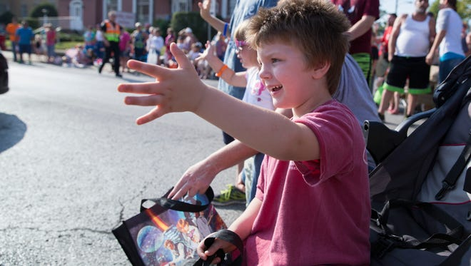 Everett Epperson, 4, waves to groups of firefighters as they pass him during the Labor Day parade in Boonville on Monday morning.