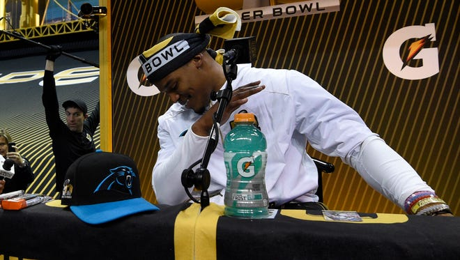 Carolina Panthers quarterback Cam Newton (1) demonstrates his dab gesture as he addresses members of the media during Super Bowl 50 Opening Night at SAP Center.