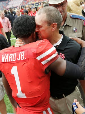 Houston Cougars quarterback Greg Ward Jr. (1) hugs head coach Tom Herman after defeating the Oklahoma Sooners in the second half at NRG Stadium.