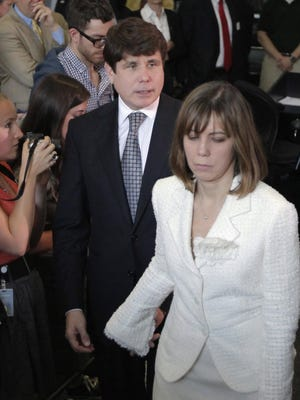Former Illinois Gov. Rod Blagojevich, led by his wife, Patti, walks to address the media after his conviction in 2011.