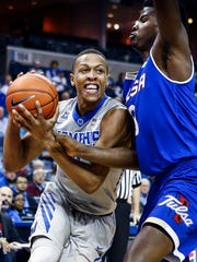 University of Memphis forward Jimario Rivers (left)