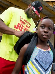 O J Howard autographs a backpack for Daria Washington at an event where he gives out backpacks to children at the Autauga Academy campus in Prattville, Ala. on Sunday July 9, 2017.