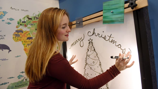 Kaylee Keogh, 18, a Sioux Falls Christian senior, volunteers at the Family Visitation Center on Dec. 12, 2016. Keogh routinely creates festive designs on the whiteboard at the center.
