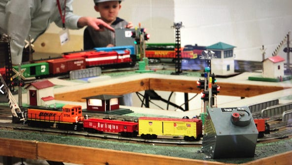 A young train enthusiast learns about a model railroading