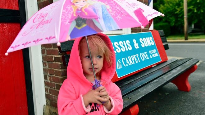 Two-year-old Makennan Robinson uses her umbrella Thursday morning to shield herself from light rain in Chambersburg. Heavy rain was expected to come later in the day Thursday and stick around through Friday. The National Weather Service issued a flood watch, in effect through 8 a.m. Friday.