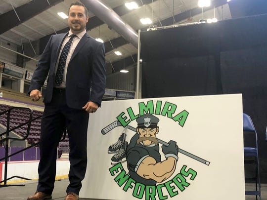 Elmira Enforcers head coach Brent Clarke stands next to the team's logo during a press conference Aug. 2 at First Arena in Elmira.