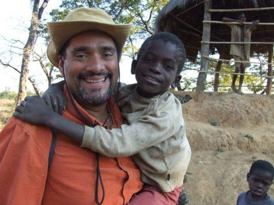 John A. Torres holds AIDS orphan Franco, while reporting in Zambia in 2006