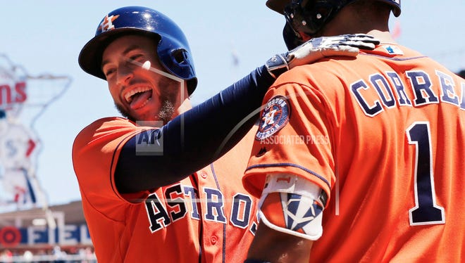 Houston Astros' George Springer, left, celebrates his solo home run off Minnesota Twins pitcher Hector Santiago with Carlos Correa in the fifth inning of a baseball game Wednesday, May 31, 2017 in Minneapolis. Correa homered in the first inning. (AP Photo/Jim Mone)