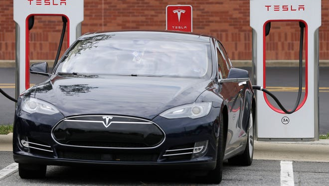 Legislation proposed Wednesday would let Tesla sell its vehicles directly from the manufacturer in Wisconsin. Pictured here, a Tesla car recharges at a charging station at a shopping center in Charlotte, N.C