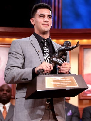NEW YORK, NY - DECEMBER 13:  Marcus Mariota, quarterback for the University of Oregon Ducks, hoist the trophy after being named the 80th Heisman Memorial Trophy Award winner during the 2014 Heisman Trophy Presentation at the Best Buy Theater on December 13, 2014 in New York City.  NOTE TO USER FOR EDITORIAL USE ONLY: Photographer approval needed for all Commercial License requests.  (Photo by Kelly Kline - Handout/Getty Images for The Heisman)