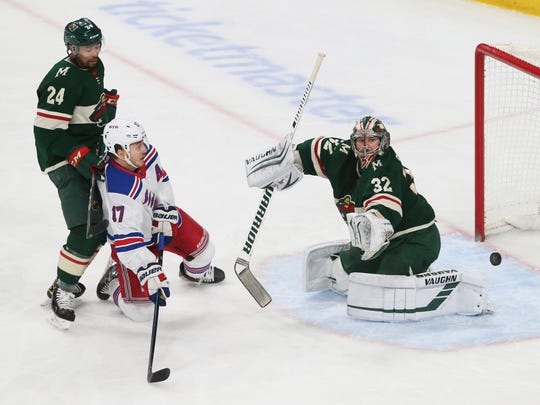 Minnesota Wild's Alex Stalock, right, blocks a shot as New York Rangers' Jesper Fast, second from left, looks for a rebound during the first period of an NHL hockey game Thursday, Feb. 13, 2020, in St. Paul, Minn. (AP Photo/Jim Mone)