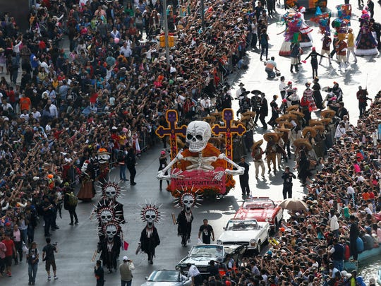 People watch the city's first Day of the Dead parade on Reforma Avenue in Mexico City, Saturday, Oct. 29, 2016. Hollywood movies, zombie shows, Halloween and even politics are fast changing Mexico's Day of the Dead celebrations, which traditionally consisted of quiet family gatherings at the graves of their departed loved ones bringing them music, drink and conversation.