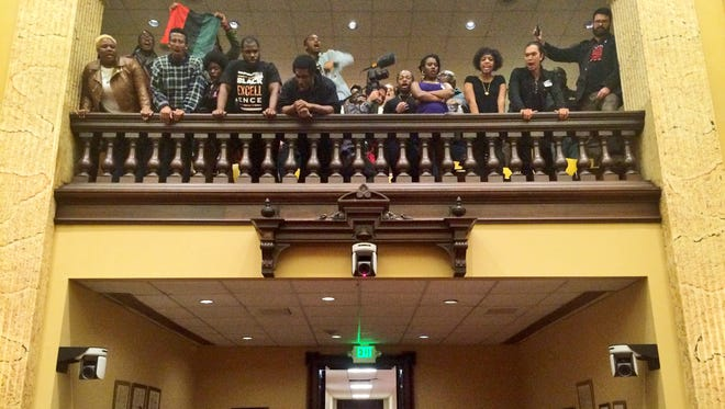 Protesters shout as council members leave the chamber at city hall in Baltimore, Wednesday, Oct. 14, 2015.