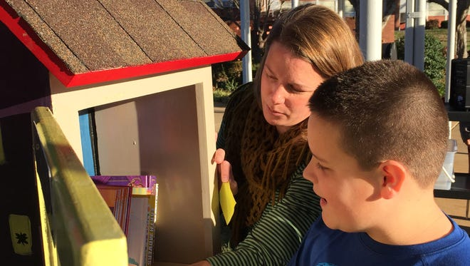 Discovery School Librarian Sarah Svarda and fifth-grader Esten Cook exchange books at the Little Free Library that opened at the school Wednesday morning.