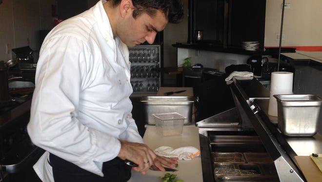 Chef and co-owner Petar Al Kurdi prepares asparagus in the open kitchen of Petar's Restaurant in Bonita Springs.