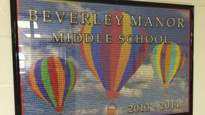 A mural made up of student yearbook photos from 2013-2014 hangs in the lobby at Beverley Manor Middle School.