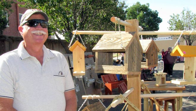 Colby Morgan of Chappy's Custom Wood, is pstured next to a tree of bird houses at the Deming/Luna County MainStreet Farmer's Market.