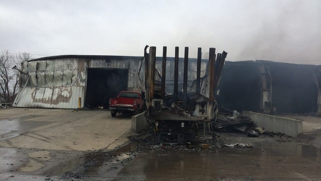 The site of Monday's industrial fire still smoldered at 2123 N.E. 46th Avenue in Des Moines.