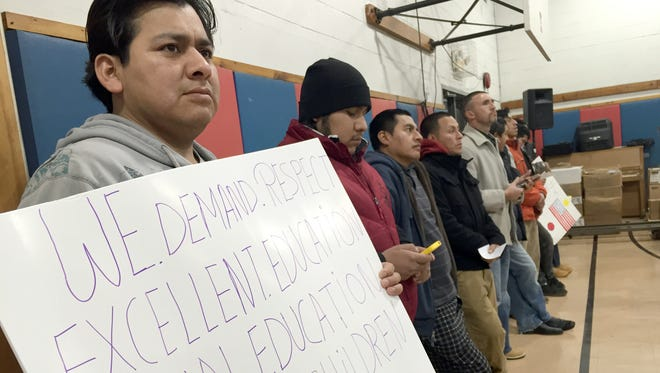 Freddy Chimbo of Spring Valley holds up a protest sign before the East Ramapo school board meeting.