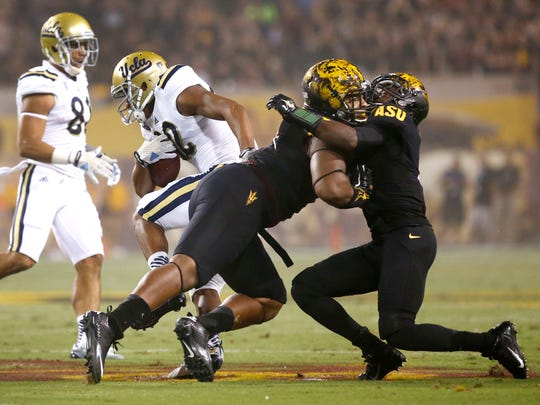 UCLA's Eldridge Massington runs for a touchdown after Arizona State's Damarious Randall (right) collides with a teammate in the first half on Thursday, Sept. 25, 2014 at Sun Devil Stadium in Tempe, Arizona.
