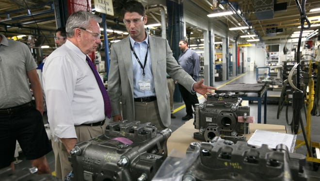 August 15, 2012 Tommy Thompson started campaigning the day after he won the republican primary with a trip to Husco International in Waukesha.  The company makes valves and hydraulic system components for the automotive and construction equipment industry.  Here Tommy Thompson (center) gets an overview on the company's product lines from Husco International CEO Austin Ramirez before giving a speech before the media and employees. MICHAEL SEARS/MSEARS@JOURNALSENTINEL.COM