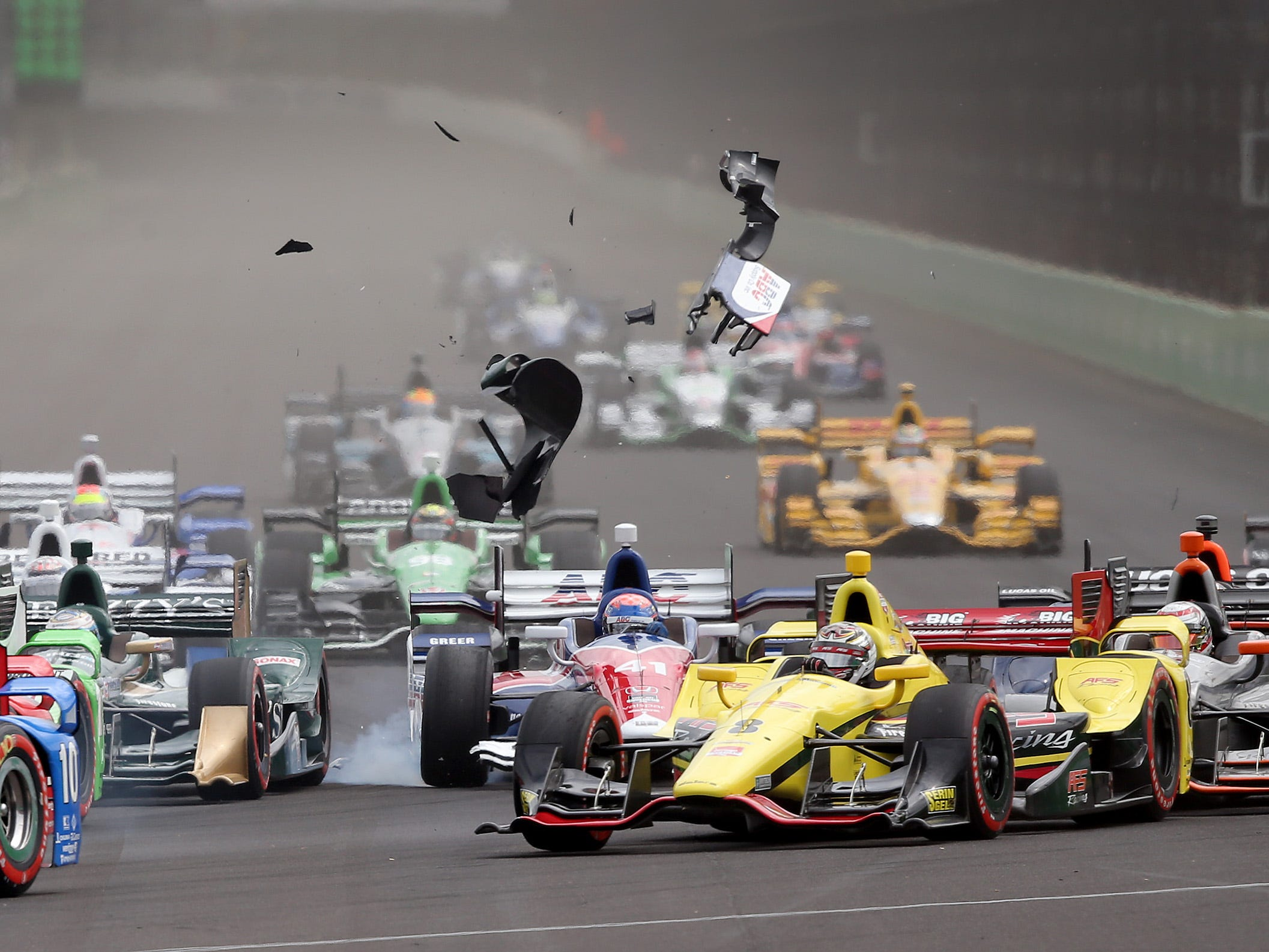 Parts fly off of A.J. Foyt EnterprisesÕ Jack Hawksworth (41) cart as the field of cars turns into turn one at the start of the the Angie's List Grand Prix of Indianapolis Saturday, May 9, afternoon at the Indianapolis Motor Speedway.