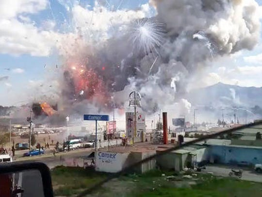 This image made from video recorded from a passing car shows an explosion ripping through the San Pablito fireworks' market in Tultepec, Mexico, Tuesday, Dec. 20, 2016. Sirens wailed and a heavy scent of gunpowder lingered in the air after the afternoon blast at the market, where most of the fireworks stalls were completely leveled. According to the Mexico state prosecutor there are at least 26 dead.