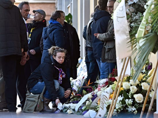 A woman lays flowers as people gather to pay their tribute to Italian player Davide Astori at the Coverciano Sports Center, near Florence, Italy, Wednesday, March 7, 2018. The 31-year-old Astori was found dead in his hotel room on Sunday after a suspected cardiac arrest before his team was set to play an Italian league match at Udinese. (Maurizio Degl'Innocenti/ANSA via AP)