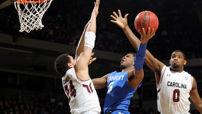 Kentucky guard Andrew Harrison (5) attempts to split South Carolina defenders Michael Carrera (24) and Sindarius Thornwell (0) in the first half half of an NCAA college basketball game, Saturday, Jan. 24, 2015, at the Colonial Life Arena in Columbia, S.C. (AP Photo/Willis Glassgow)