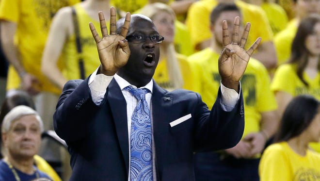 Michigan basketball assistant coach Bacari Alexander signals against Delaware State on Dec. 12, 2015, in Ann Arbor.