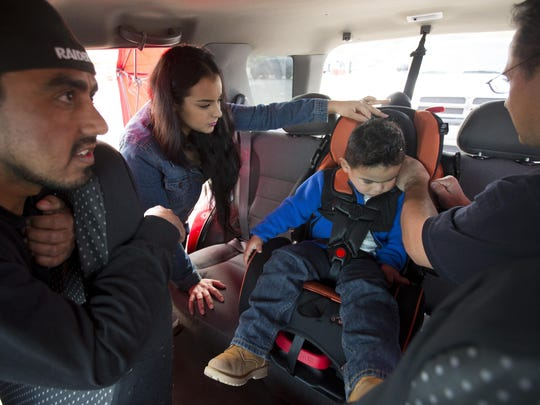 Manuel Perez, left, and Yuni Pena, learn how to properly install a car seat for their 2-year-old son, Manuel, from Phoenix Fire engineer Dean Bradford, right, during The Safe Kids Coalition of Maricopa County event at South Mountain Park in Phoenix on February 23, 2015.