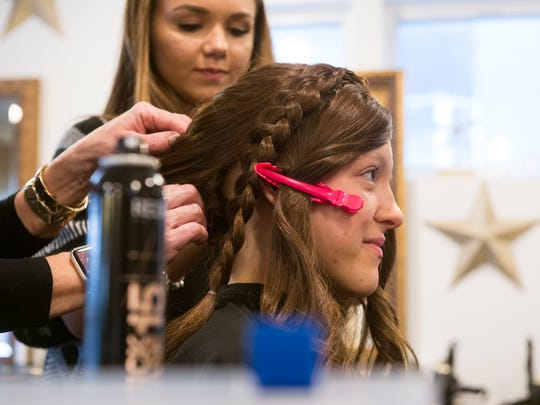 Nicole Eckard works on braiding Alyssa White's wig for her high school prom, Wednesday, April 25, 2018. White lost her hair after undergoing chemotherapy to treat Hodgkin's lymphoma, which she was diagnosed with in Jan. 2017.