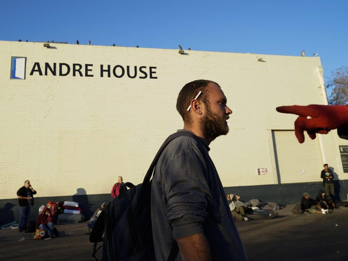 Homeless men and women wait in line outside Andre House