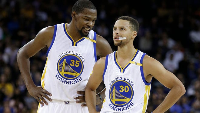 Golden State Warriors' Kevin Durant, left, speaks with Stephen Curry (30) during the first half of a pre-season NBA basketball game against the Los Angeles Clippers in Oakland, Calif.