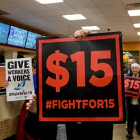 Supporters of a $15 minimum wage walk through a Dunkin' Donuts store during a rally Nov. 10 at the Capitol in Albany.