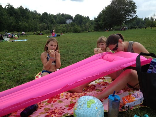Monica Boyd of Northfield blows up an inflatable while her daughters Olivia, 7, and Natalie, 5, eat lunch at Waterbury Reservoir.