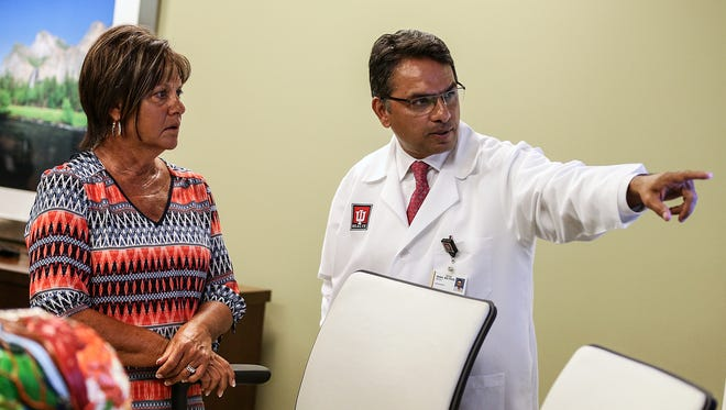 From left, Lisa Foster and Dr. Mitesh Shah watch a video clip recorded during Foster's March surgery, at the IU Health Neuroscience Center, Indianapolis, Monday, July 17, 2017. In March, a BrightMatter robotic arm holding a camera assisted Shah in an eight-hour surgery to remove an uncommonly located meningioma tumor deep in Foster's brain, where the cervical spine and brain stem meet.