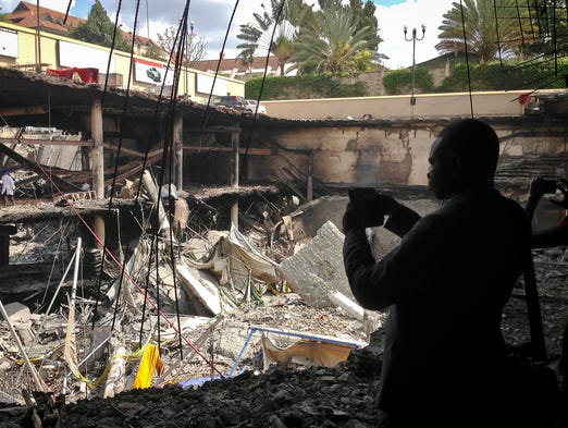A person photographs the collapsed upper parking garage at the Westgate mall on Oct. 1 in Nairobi, Kenya. Gunmen took over the mall on Sept. 21 and killed 67 people.