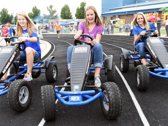 Abby Martin, from left, Abby Dietsche and Emma Martin start a race on peddle go-carts Friday evening at BomberFest.