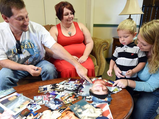 Johnny McKenzie, left, shows a photograph of his son, Michael, to Michael's two-year-old son Tye. Michael died after being struck by a car on Aug. 21. Also pictured are Michael's mother, Deborah, second from left, and Tye's mother, Jessica Miller.